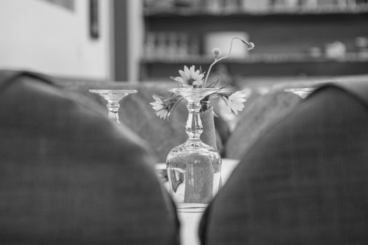 Upside Down Wine Glass Behind the Flower Grayscale Photo