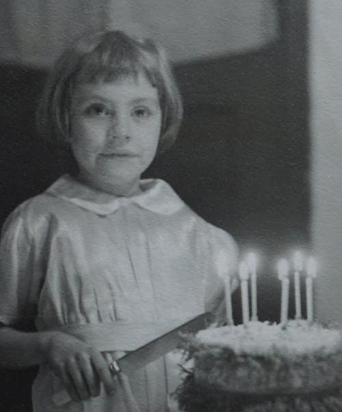 Girl in White Dress Holding Birthday Cake