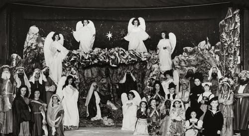 Grayscale Photo of Children Wearing Costumes At A Christmas Presentation