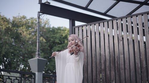 Woman in Hijab Playing Violin