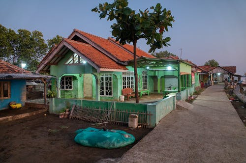 Aged dwelling building exteriors with growing trees in garden against empty walkway in evening