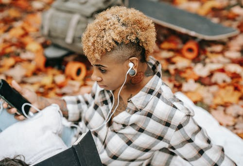 From above of African American female with earphones and smartphone sitting on blanket near skateboard and backpack on blurred background in autumn park