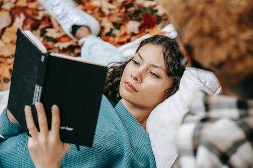 From above of pensive Hispanic female reading book while lying on lap of crop person while spending free time together in autumn nature