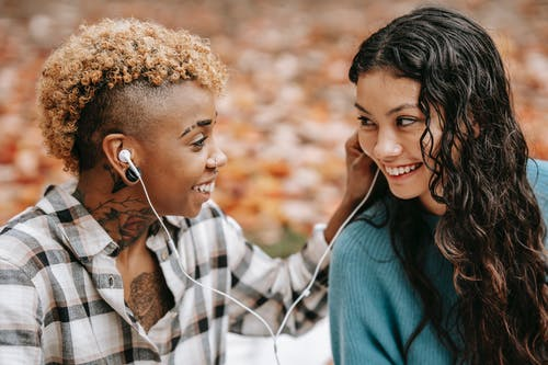 Side view of loving African American woman giving earphone to smiling Hispanic girlfriend while looking at each other during romantic date in autumn forest on blurred background