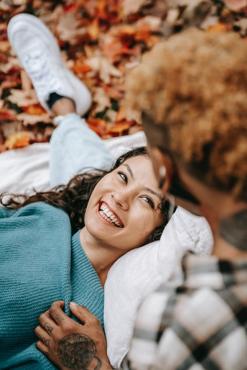From above of smiling Hispanic female looking at unrecognizable person with love while lying on blanket in autumn forest with fallen leaves
