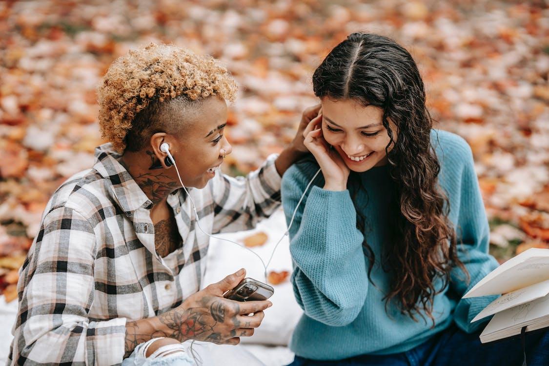 Happy multiethnic friends listening to music in earphones in park