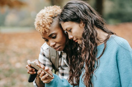 Charismatic lesbian couple browsing mobile phone