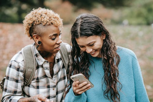 Happy diverse lesbian couple with smartphone