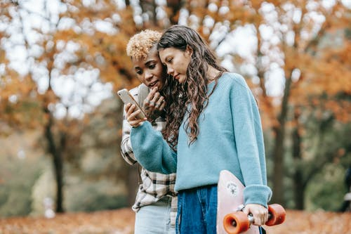Multiracial lesbian couple standing in fall park with smartphone and longboard while attentively looking at screen