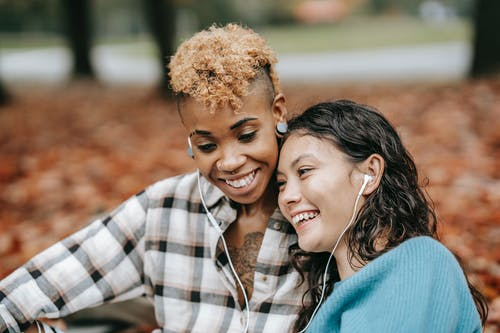 Cheerful African American woman with Hispanic girlfriend using earphones while listening to music in autumn park on blurred background during date