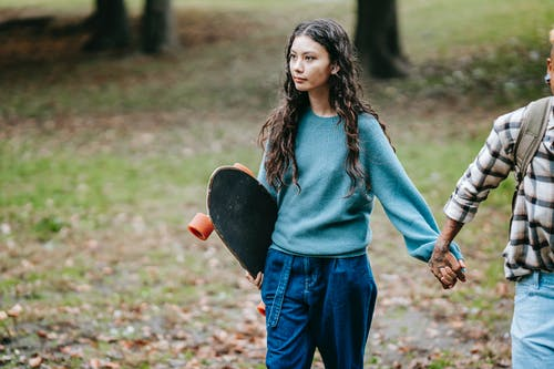 Hispanic woman with longboard walking with crop partner
