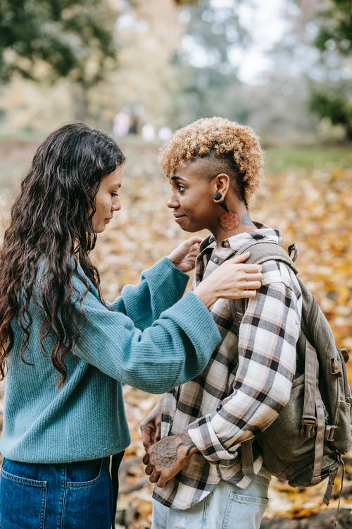 Side view of caring Hispanic woman adjusting backpack of content African American girlfriend while standing in autumn forest on blurred background