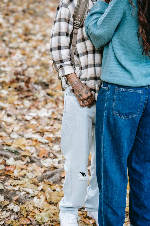 Unrecognizable tattooed person with backpack standing close to anonymous partner while spending time in autumn forest with fallen leaves during date