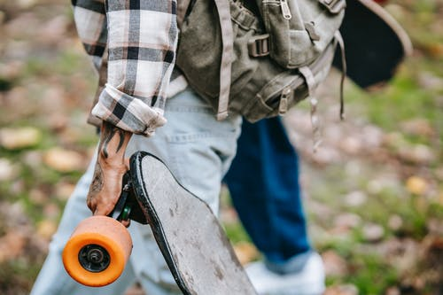 Unrecognizable tattooed person with longboard and backpack strolling with anonymous partner during weekend in park on blurred background