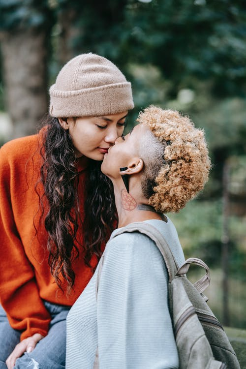 Loving multiracial lesbian couple with closed eyes caressing in park