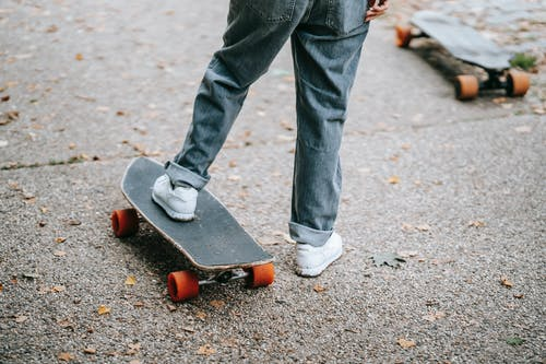 Crop anonymous skater in jeans and sneakers standing on skateboard on asphalt road on street in daytime