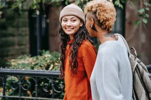 Young informal female talking with girlfriend while walking together