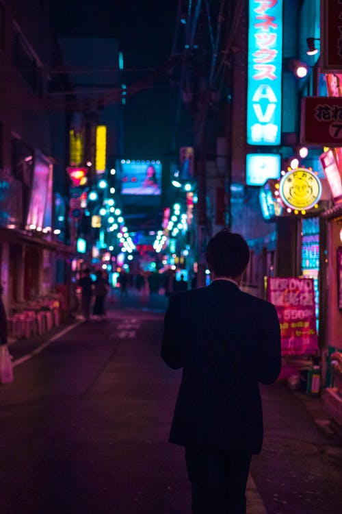 Man in Black Suit Walking on Street during Night Time