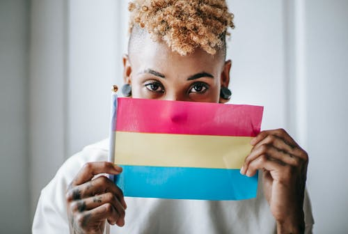 Black tattooed woman showing Pansexual pride flag