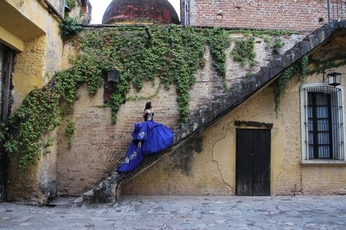 Woman in Blue Gown Standing on Concrete Staircase