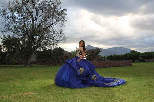 Woman in Blue Gown Standing on Green Grass Field