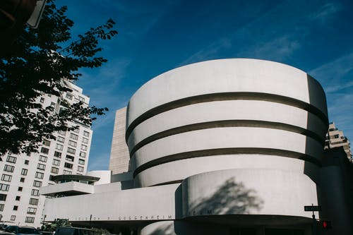 Exterior of white modern museum of art with round shape located on street in city against residential building and blue sky