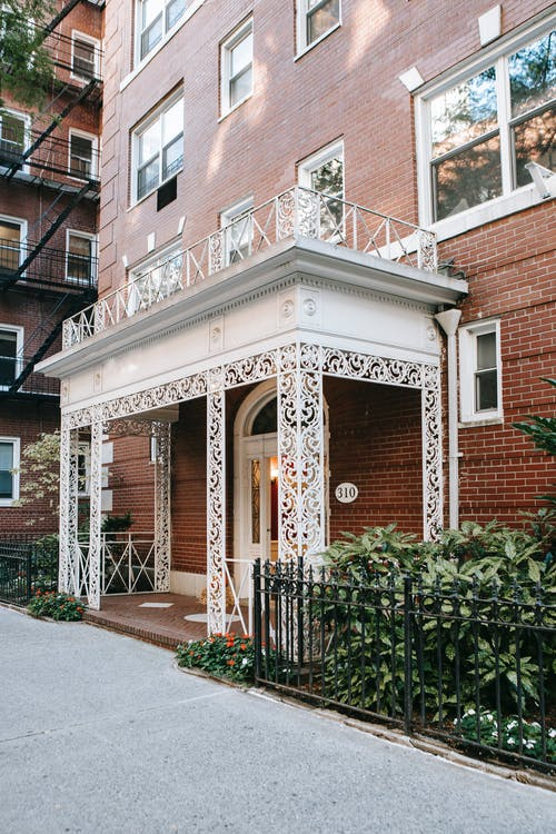 Exterior of residential brick house with white ornamental terrace located near metal fence with green plants in city on street