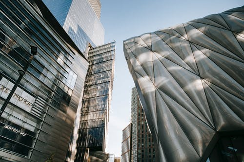 From below of contemporary office center with transparent walls located near futuristic building against blue sky in city on street