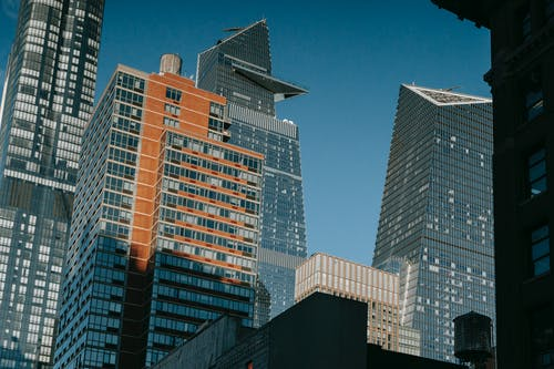 From below of contemporary high buildings with glass windows and modern design located against blue sky in city on street