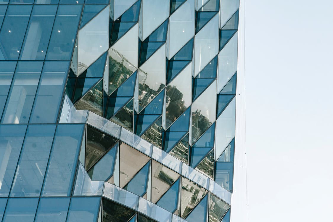 Corner of contemporary geometric building with reflection of cityscape on big glass transparent walls located on city street against cloudless sky
