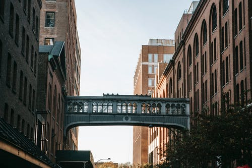 Narrow street with metal overpass connecting brick apartment houses against cloudless sky in city street in residential area on sunny day
