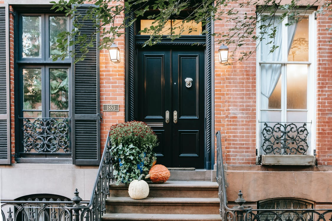 Entrance of residential building with pumpkins on stone stairway near black door and windows on brick wall located in street