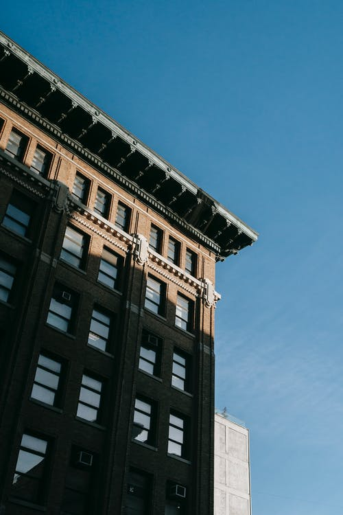 From below of corner of apartment building with roof cornice located against blue sky in city on street in sunlight