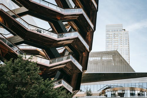 Low angle of futuristic geometric construction with stairs above bushes in city with skyscrapers in daylight
