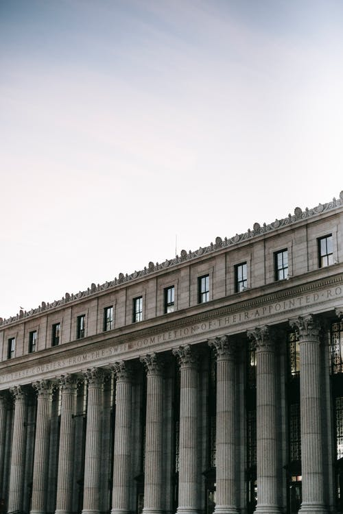 Low angle of exterior of historic James A. Farley Post Office with pillars and windows in center of New York City in soft daylight