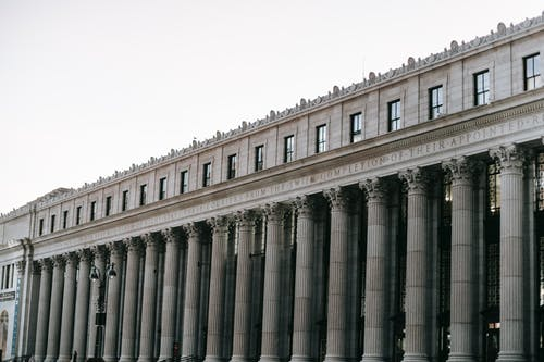 From below of facade of famous James A Farley Post Office with columns and windows in center of New York at daytime