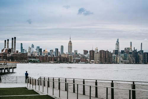 Man standing on embankment of river in big city