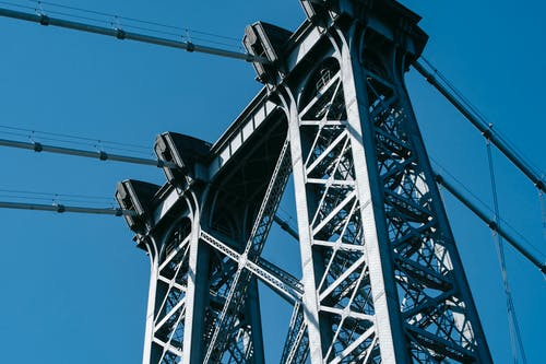From below of suspension Williamsburg Bridge with long metal constructions against cloudless sky