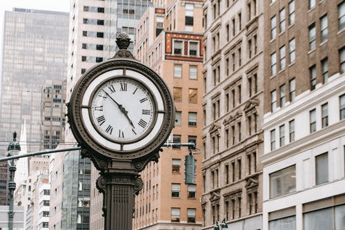 Vintage street clock on pillar located near residential buildings and skyscrapers in downtown of New York city in financial district