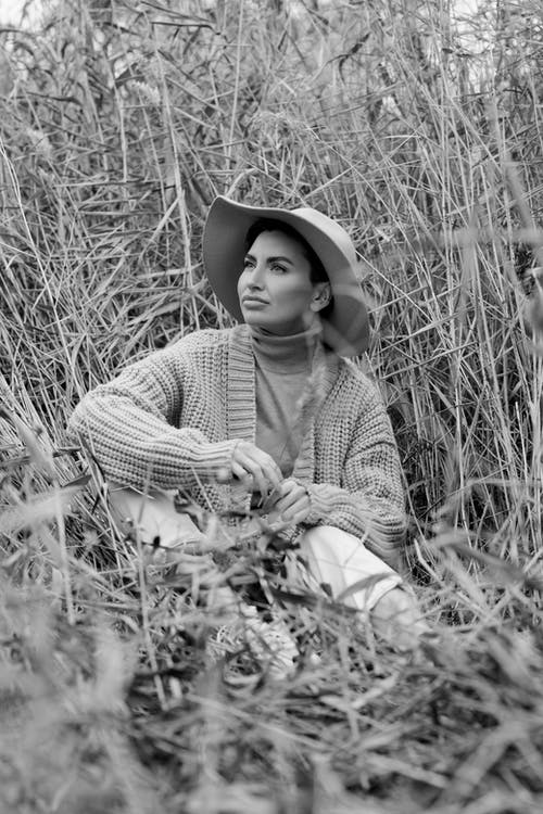 Grayscale Photo of Woman in Long Sleeve Shirt and Hat Sitting on Grass Field