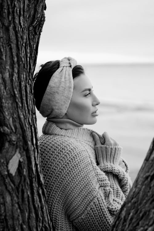 Grayscale Photo of Woman in Knit Sweater Leaning on Tree