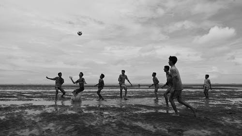 Silhouette of People Playing Soccer on Beach