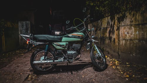 Green and Black Standard Motorcycle Parked Beside Brown Concrete Wall