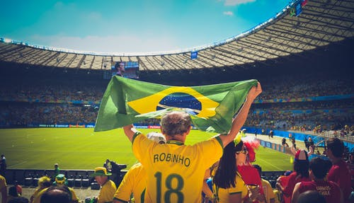 Man Raising Brazil Flag Inside Football Stadium