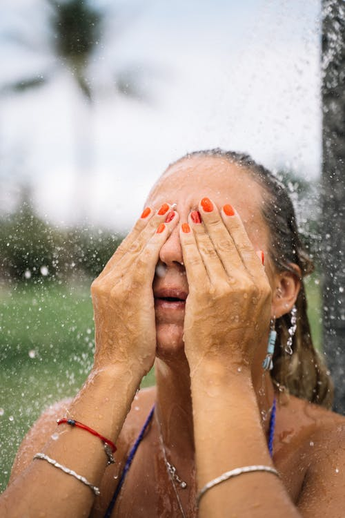 Girl in Blue Tank Top Covering Her Face With Her Hand