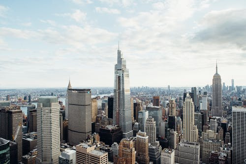 Drone view of modern high rise houses and empire state building located against cloudy sky in downtown of New York city