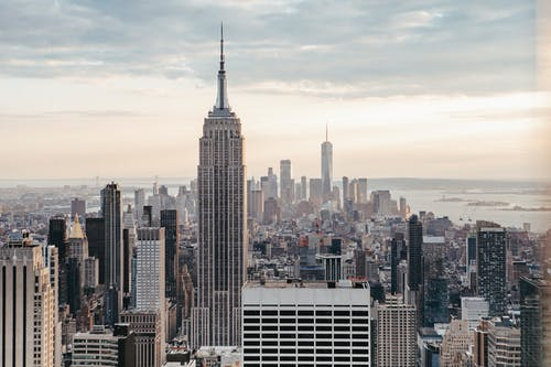 Empire State Building near multistage houses against ocean