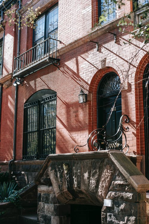 Exterior of brick residential building with arched door and stone stairs located on city district on sunny day