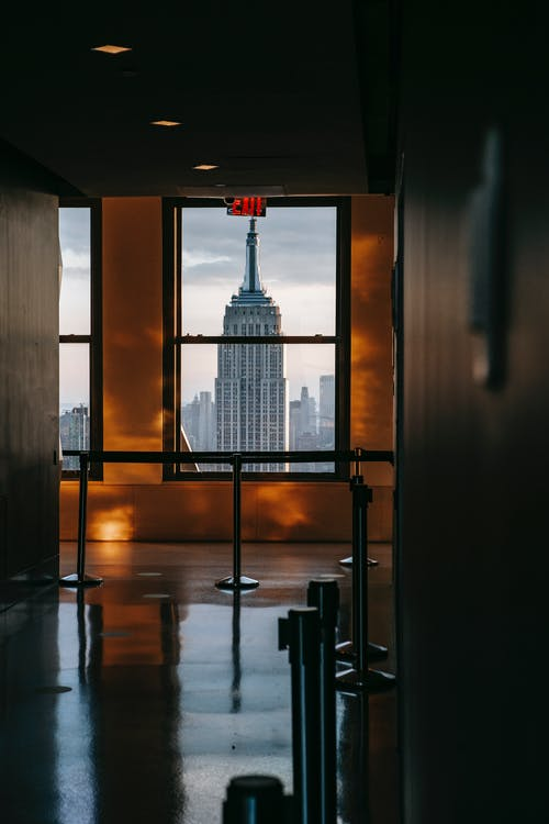 Empty hallway of modern building with metal railings and windows overlooking Manhattan with famous skyscraper in New York