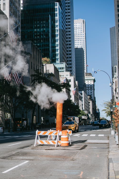 Steam pipe on road among skyscrapers on sunny day